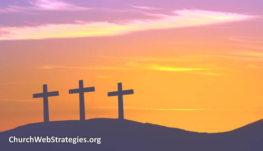 three crosses silhouetted on hill sunset