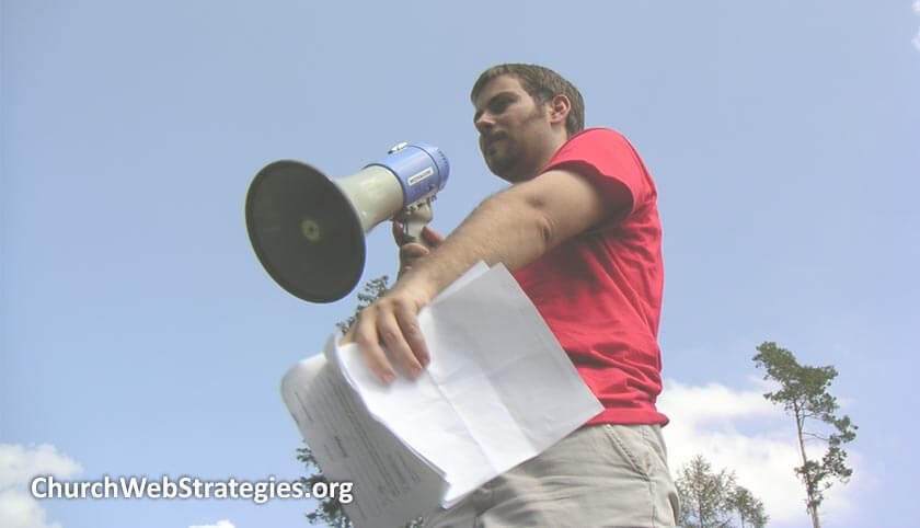 man outside holding papers and a megaphone