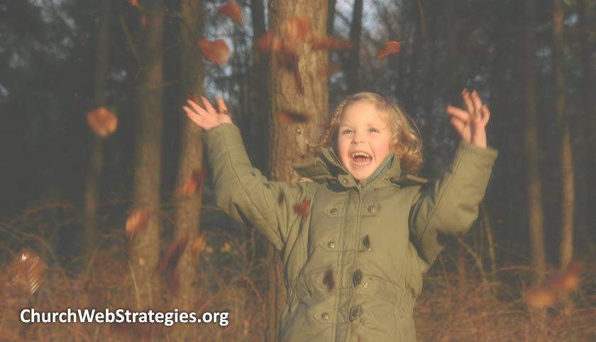 laughing child throwing leaves in air